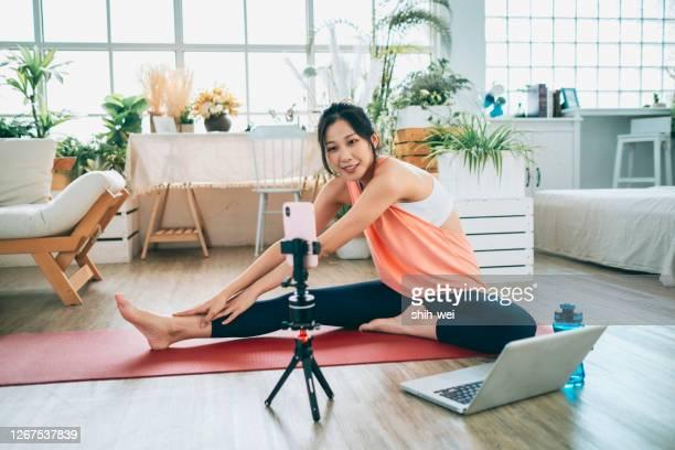 自宅でラップトップの前でストレッチ運動をしている若い女性 - 三脚 ストックフォトと画像