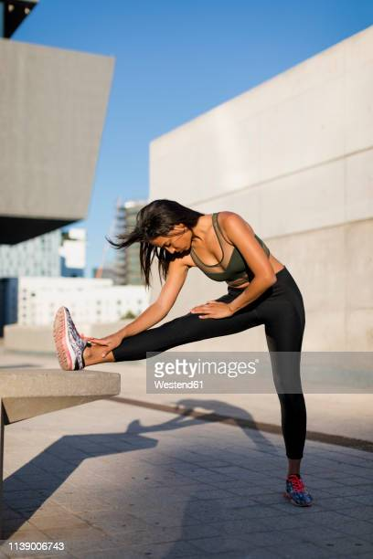 young woman doing stretching exercise in the city - bend over woman stock pictures, royalty-free photos & images