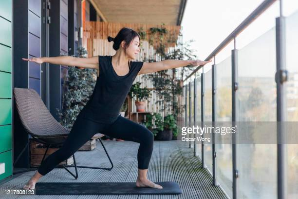 young woman doing stretching exercise on the balcony - yoga stock pictures, royalty-free photos & images