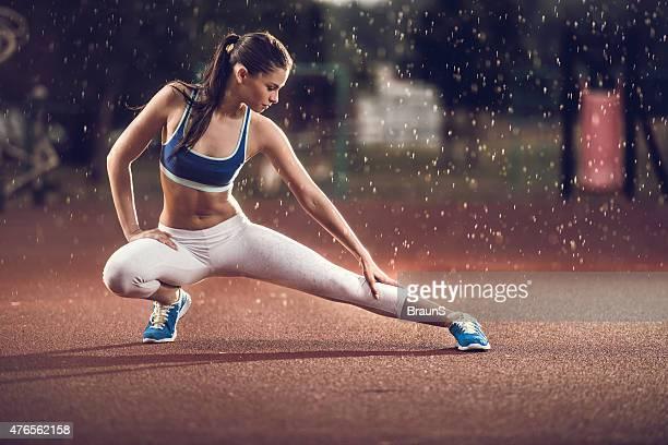 Jeune femme de faire des exercices d'étirement sur la pluie.