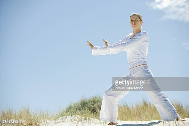 Young woman doing Tai Chi in dunes, full length
