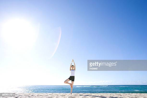 Young woman doing tree pose of yoga asana on beach