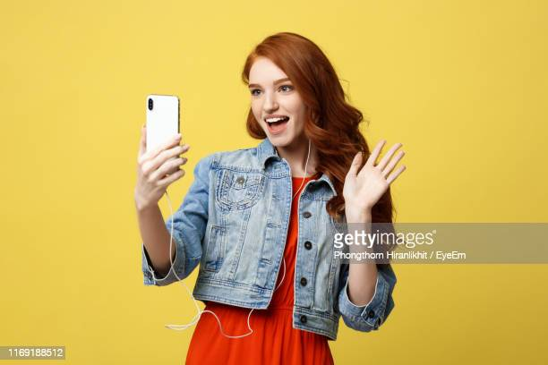 young woman doing video conference against yellow background - 手を振る ストックフォトと画像