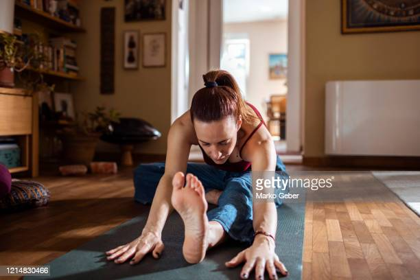 young woman doing yoga at home - vita attiva foto e immagini stock