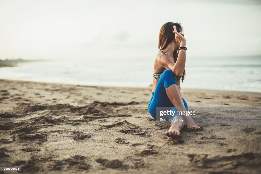 Young Woman Doing Yoga At The Beach : Stock Photo