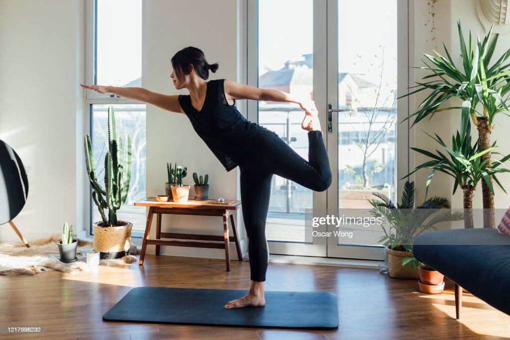 Young woman doing yoga exercise at home : Stock Photo