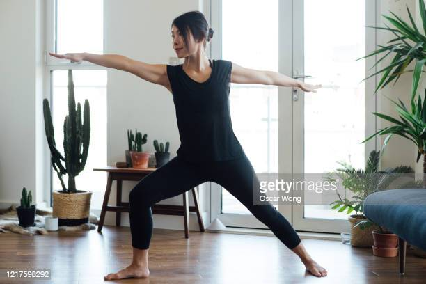 young woman doing yoga exercise at home - home workout stock pictures, royalty-free photos & images