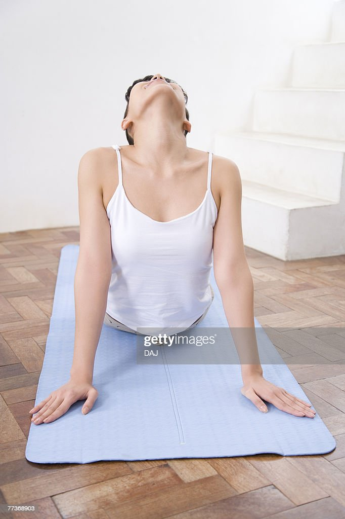 Young woman doing yoga exercise, stretching, front view   : Photo