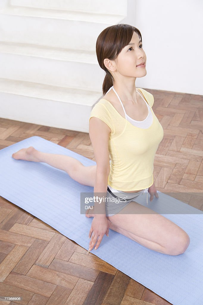 Young woman doing yoga exercise, stretching, high angle view   : Photo