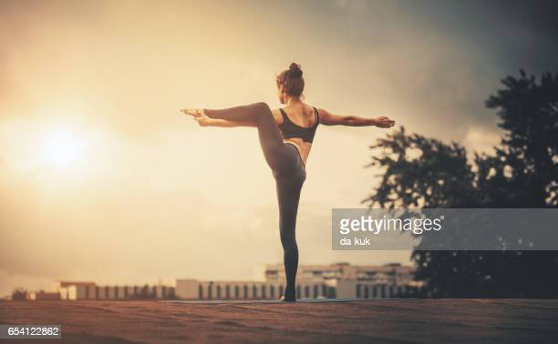 young woman doing yoga exercises at sunset - tree position stock photos and pictures
