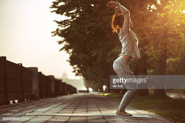 Young Woman Doing Yoga Exercises in Park