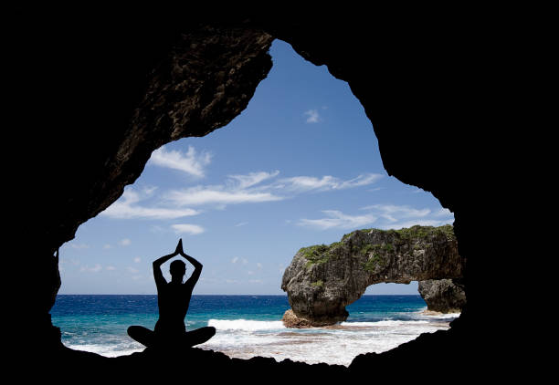 Young woman doing yoga in a cave