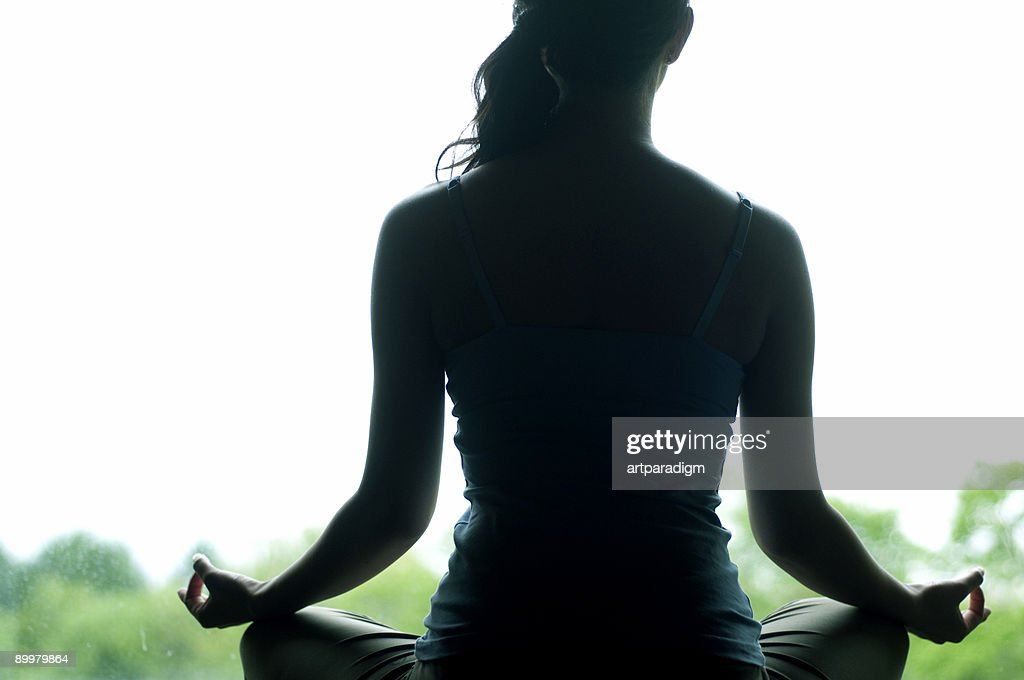 Young woman doing yoga in front of window : Stock Photo