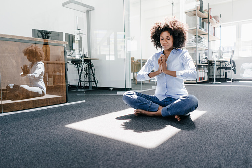 Young woman doing yoga in office - gettyimageskorea