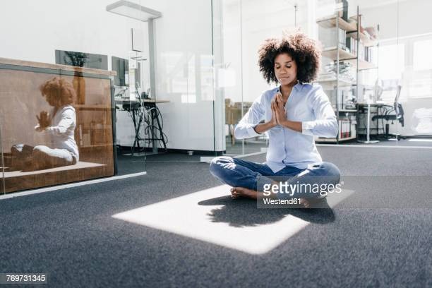 young woman doing yoga in office - meditieren stock-fotos und bilder
