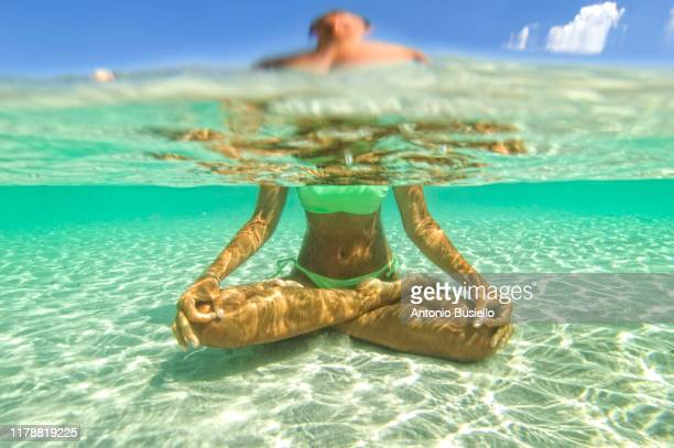 young woman doing yoga in the water - alternative pose stock pictures, royalty-free photos & images