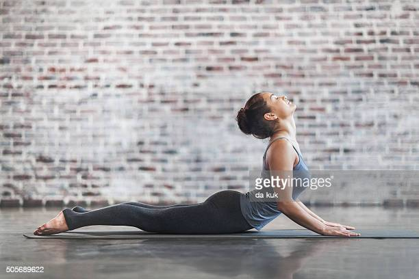 young woman doing yoga meditation and stretching exercises - yoga stockfoto's en -beelden