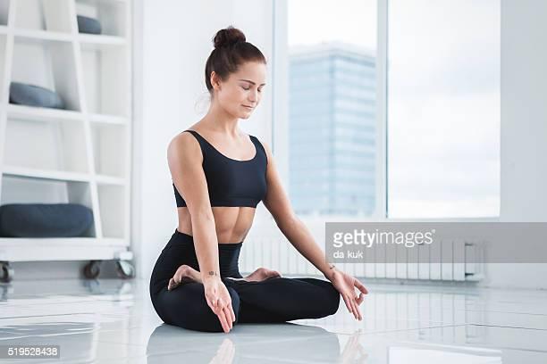 Young Woman Doing Yoga Meditation Exercise. Lotus Position
