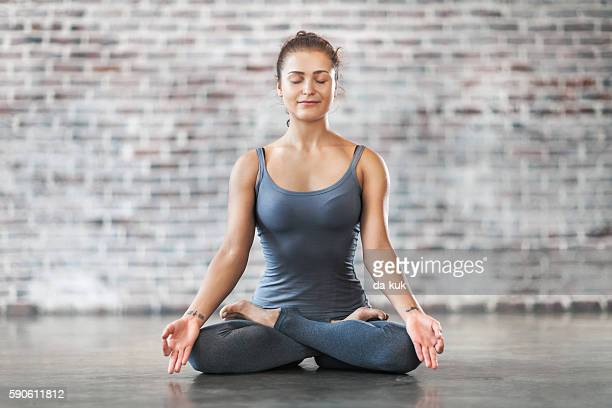 Young Woman Doing Yoga Meditation Exercise. Lotus Position