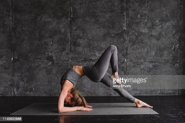 young woman doing yoga on a gray background - gymnastics poses stock pictures, royalty-free photos & images