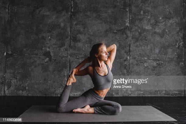 young woman doing yoga on a gray background - yogi stock photos and pictures