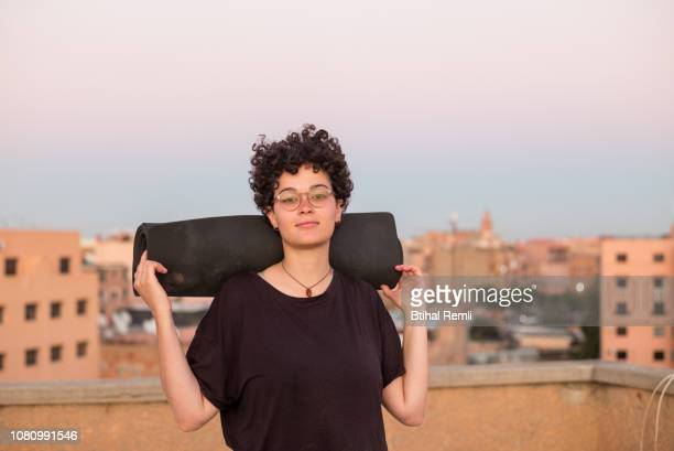 young woman doing yoga on a rooftop