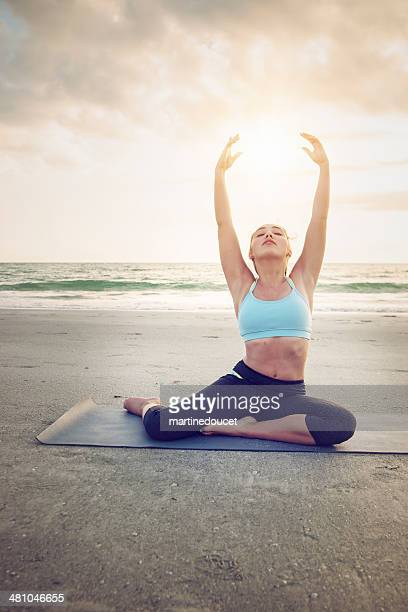 Young woman doing yoga on beach at sunset.