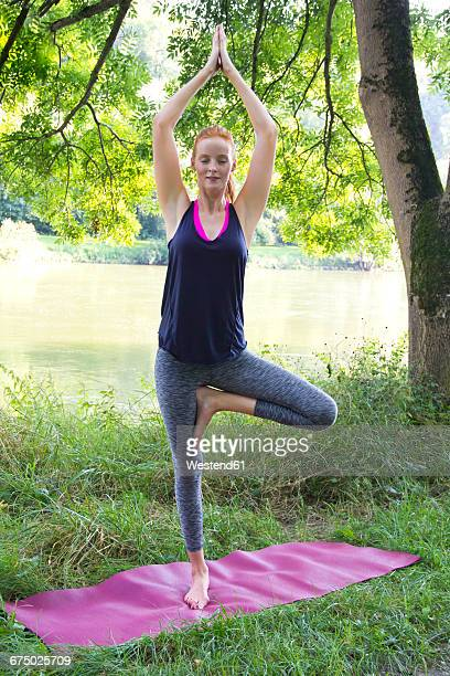 Young woman doing yoga on gym mat on a meadow