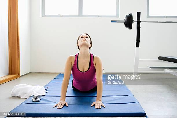 Young woman doing yoga on mat in gym