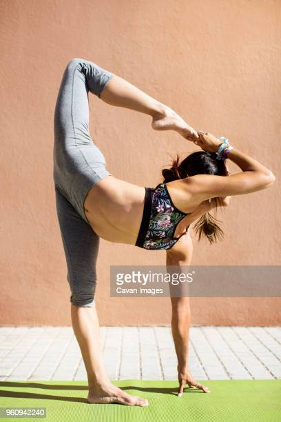 Young woman doing yoga on sidewalk