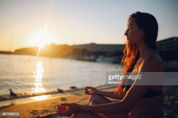 Jonge vrouw doet yoga op het strand in Rovinj