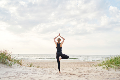 Young woman doing yoga on the beach 1129177104