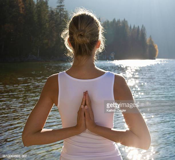 Young woman doing yoga pose, rear view