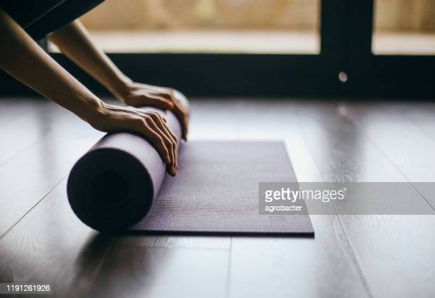 young woman doing yoga twist mat healthy lifestyle - mat stock pictures, royalty-free photos & images