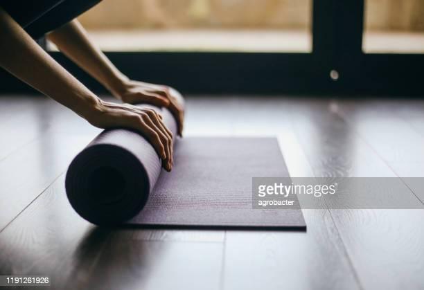 ヨガツイストマット健康的なライフスタイルをやっている若い女性 - エクササイズマット ストックフォトと画像