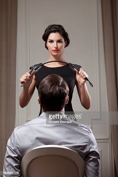 young woman dominating - women whipping men stock photos and pictures