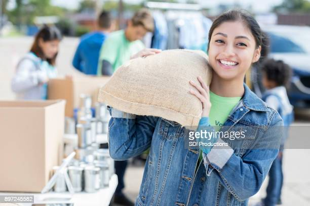 young woman donates bag of food during food drive - humanitarian aid stock pictures, royalty-free photos & images
