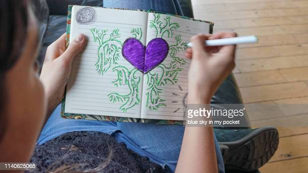 A young woman drawing a heart in her diary.