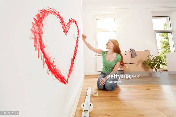 Young woman drawing a heart on a wall in new apartment