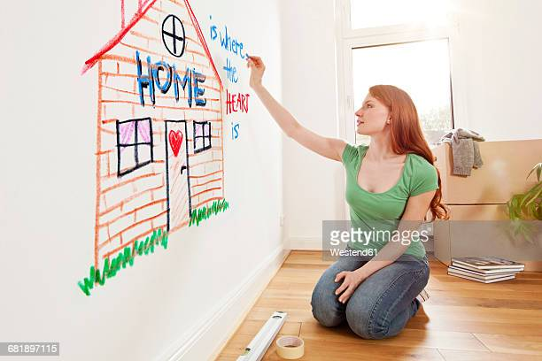Young woman drawing a house on a wall in new apartment