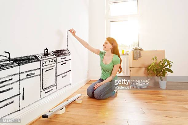 Young woman drawing a kitchen on a wall in new apartment