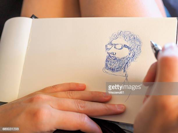 Young woman drawing a portrait of a man