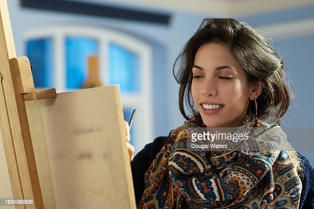 Young woman drawing at easel.