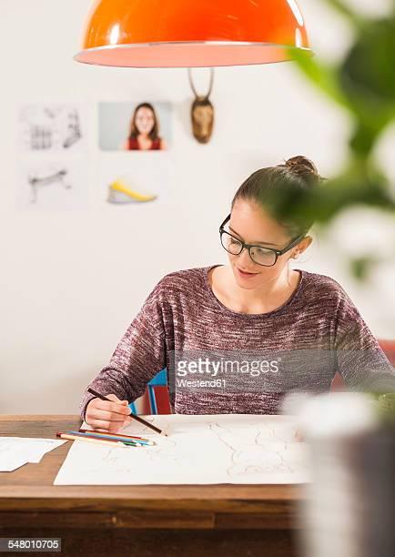 Young woman drawing at home