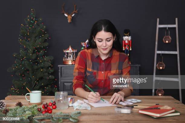 Young woman drawing Christmas card with pencil