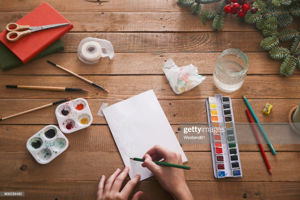 Young Woman Drawing Christmas Card With Pencil Top View Stock Photo