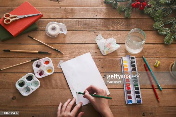 Young woman drawing Christmas card with pencil, top view