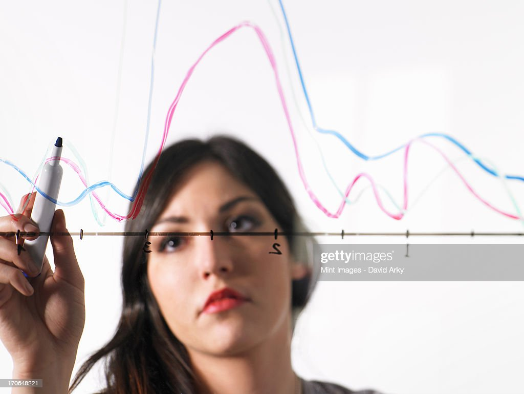 A young woman drawing coloured graph lines across a graph illustration, on a see through surface. : Stock Photo