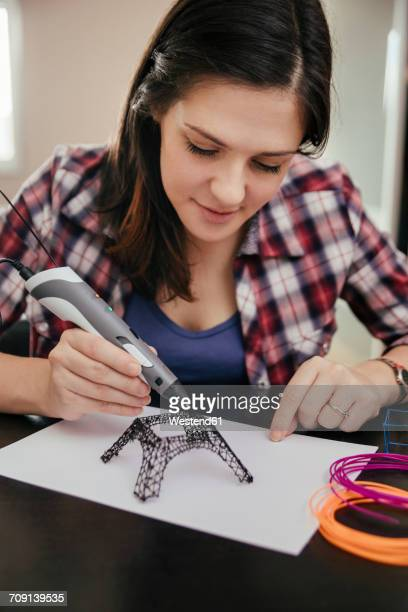 Young woman drawing Eiffel Tower with 3D pen