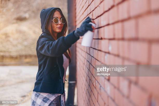 young woman drawing graffiti on the brick wall - street artist stock photos and pictures